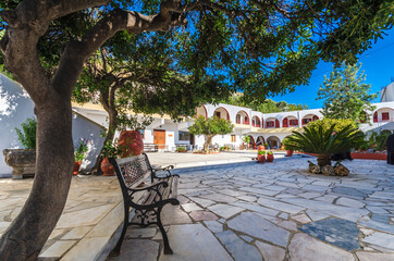 Beautiful quad  of a cretan monastery with bench trees flowers and monk cells.