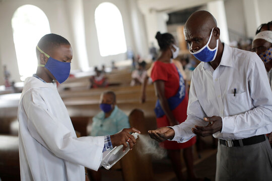 An altar, wearing a face mask, boy sprays to sanitise the hands of a Catholic faithful before taking communion during a mass on the first day of the reopening of temples and worship places, amid the coronavirus disease (COVID-19) outbreak, at the Cathedral