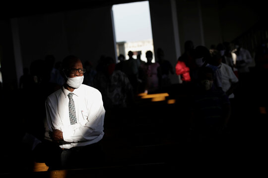 A Catholic faithful, wearing a face mask, attends to a mass on the first day of the reopening of temples and worship places, amid the coronavirus disease (COVID-19) outbreak, at the Cathedral of Port-au-Prince