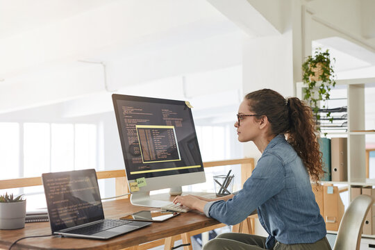 Side view portrait of female IT developer typing on keyboard with black and orange programming code on computer screen and laptop in contemporary office interior, copy space