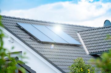 Photovoltaik auf einem Hausdach mit Lichtreflex der Sonne