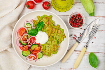 Delicious healthy green waffles with zucchini, spinach and Basil. It is served with a salad of fresh vegetables-tomatoes, cucumbers and red onions with olive oil and spices. Selective focus, top view