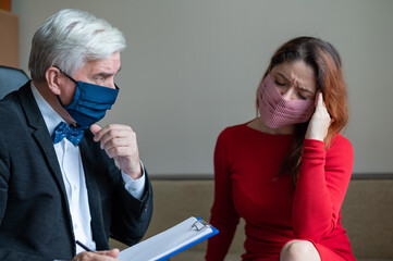 Male psychotherapist advises a female client in a medical mask. Moral support during the epidemic....