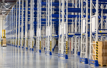 Wall Mural - Perspective of Huge distribution warehouse with high empty shelves and forklift.