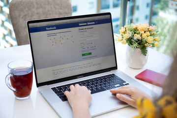 Woman hand Macbook Pro 16 with social networking service Facebook