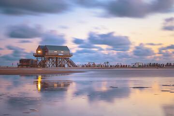 Strand von Sankt Peter-Ording in der Abenddämmerung mit Pfahlbau