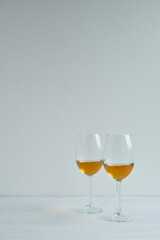 Poster Alcohol Glasses with white wine staying on the wight background