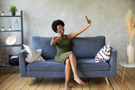 Happy african American young woman sit relax on cozy couch happy to move to new apartment. Smiling black girl rest on comfortable sofa in living room dreaming
