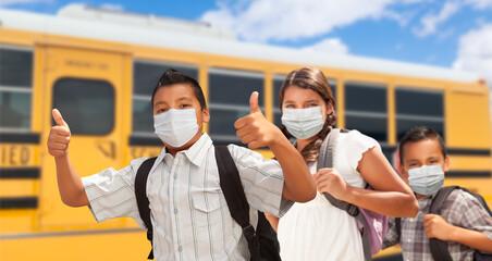 Hispanic Students Near School Bus Wearing Face Masks