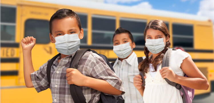 Hispanic Students Near School Bus Wearing Face Masks