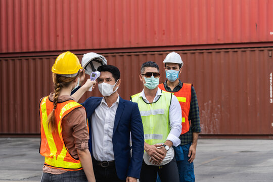 Engineer worker wearing surgical mask checking body temperature using infrared digital thermometer check temperature before into workplace, workers with protective mask