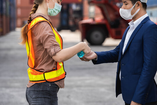 The supervisor wearing a protective surgical mask, standing for a physical examination and pressing the alcohol gel to colleague before into workplace at the warehouse container.