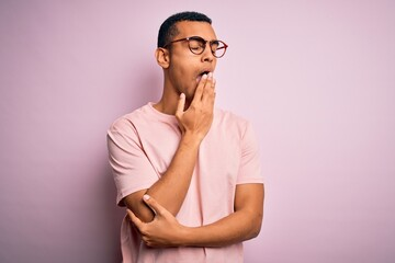 Handsome african american man wearing casual t-shirt and glasses over pink background bored yawning tired covering mouth with hand. Restless and sleepiness.