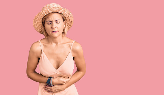 Young blonde woman wearing summer hat with hand on stomach because indigestion, painful illness feeling unwell. ache concept.