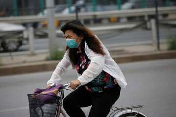 Woman wearing a face mask rides a bicycle on a street during morning rush hour, following the outbreak of the coronavirus disease (COVID-19), in Beijing