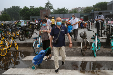 People wearing face masks are seen on a street, following the outbreak of the coronavirus disease (COVID-19), in Beijing