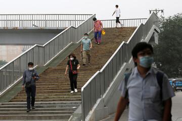 People wearing face masks walk down an overpass, following the outbreak of the coronavirus disease (COVID-19), in Beijing