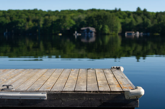 Perspective of a wooden dock on a calm lake in Muskoka, Ontario Canada.