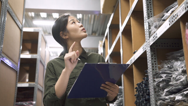 Candid of young attractive asian woman working in warehouse store counting and stock taking inventory by clipboard paper. entrepreneur small business SME concept. lady staff standing in storehouse.