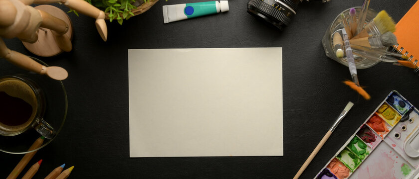 Artist workspace with mock up sketch paper, painting tools, camera and decoration on black desk
