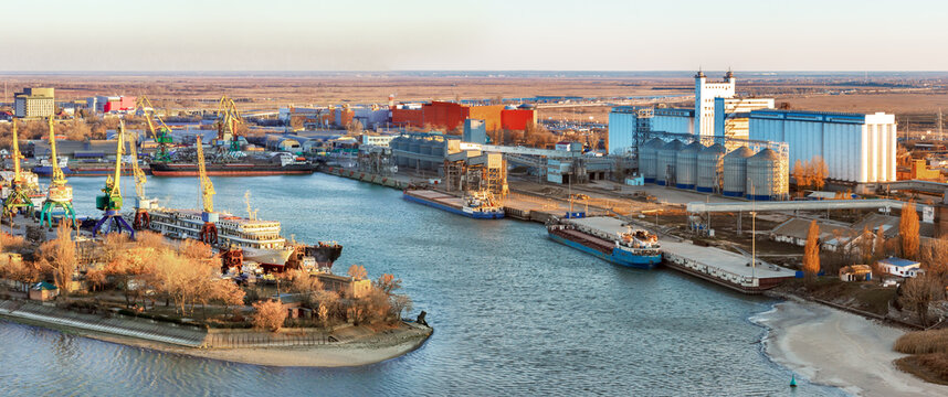 The panoramic view the river harbor with the big industrial building of grain elevator and  a cargo berth for loading grain onto bulk-carriers. International wheat trade