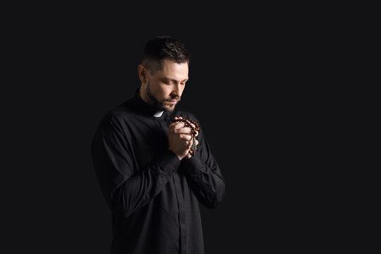 Handsome praying priest on dark background