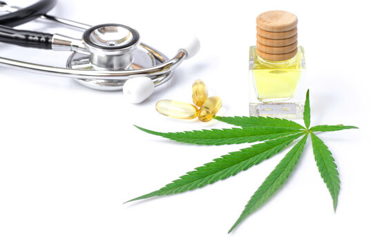 Cannabis hemp essential oil extracted and capsules with fresh organic marijuana green leaf and medical stethoscope isolated on white background.