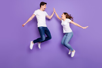 Full length profile side photo of cheerful two people freelancer jump win discount clap high five gesture wear white t-shirt denim jeans gumshoes isolated over violet color background