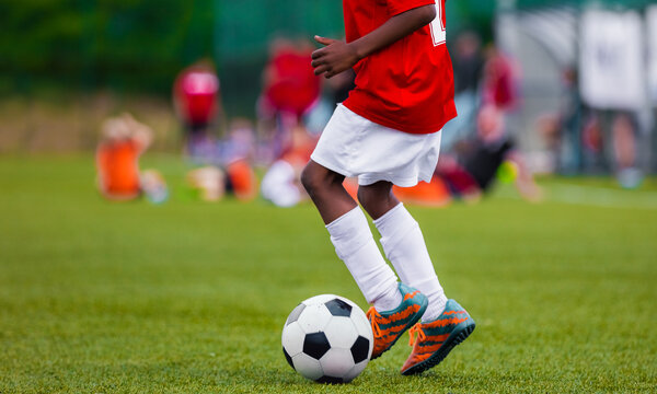 African American Boy in Junior Football Team Leading Ball on Grass Training Field. Youth Soccer Player Kicking Ball
