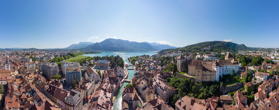 Annecy city center panoramic aerial view with the old town, castle, Thiou river and mountains surrounding the lake, beautiful summer vacation tourism destination in France, Europe