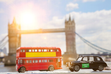 Close-up view of public transport figurines with Tower Bridge in the background