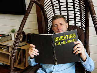 Man reads investing for beginners book at home.