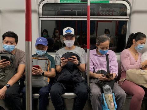 Passengers wear surgical masks in an MTR train in Hong Kong