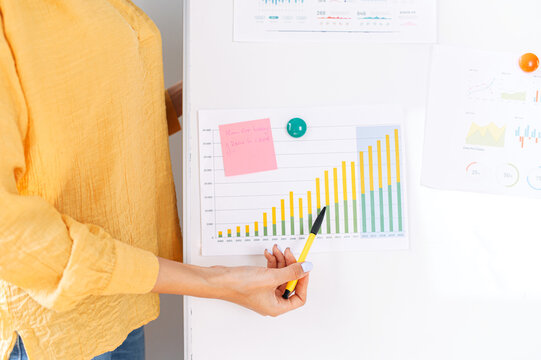 A graph with some raising statistics datas hangs on flip chart, a female hand with a pencil points on it