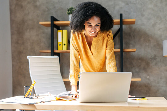Charming african-american young woman uses a laptop in modern office, the woamn in smart casual wear leaned on the desk and focused on a screen