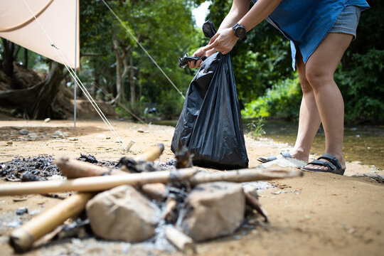 Asian people collecting litter with garbage bag at the national park,tourist pick up trash waste after camping in nature forest,tent and stream in background,caring for environment,ecology protection