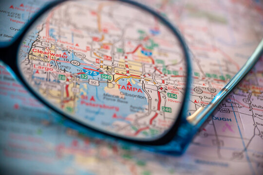 WOODBRIDGE, NEW JERSEY - July 13, 2020: A map of Florida is shown with a focus on Tampa through a pair of eyeglasses