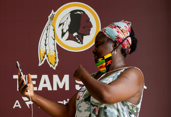 Woman takes selfie in front of Washington Redskins logo at FedEx Field in Landover, Maryland