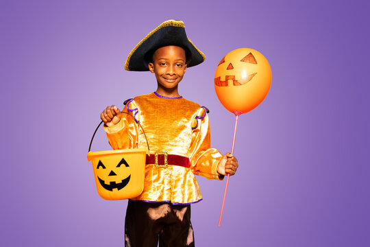 Little cute black boy in Halloween costume show smiling and standing over purple background holding scary candy bucket