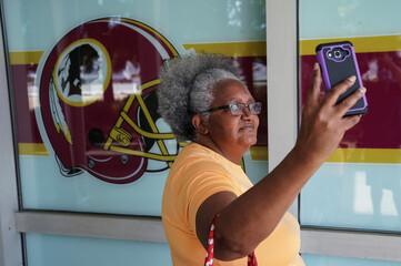 Fan takes selfie in front of Washington Redskins logo at FedEx Field in Landover, Maryland