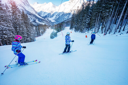 Group of children on the mountain ski down in school formation