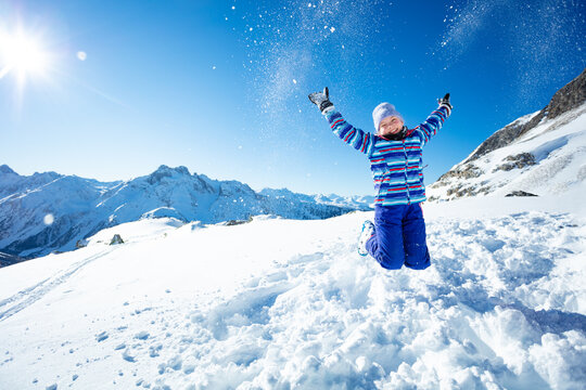Beautiful young ski girl jump in mid-air and throw snow up over blue sky