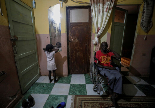 Sundanese refugee Ayat Mohamed's sick father sits on a wheelchair at their home in Ain Shams district, amid concerns about the spread of the coronavirus disease (COVID-19) in Cairo