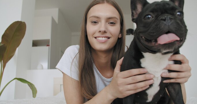 woman sit at home with black french bulldog