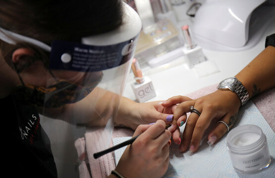 Jessy works on a client's manicure at Luxe Beauty nail salon, in Winnington