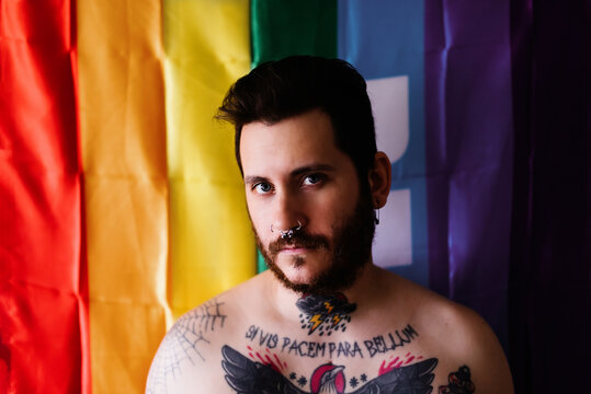 young caucasian boy half-naked and tattooed poses on camera in front of a lgbt pride flag. lgbt concept