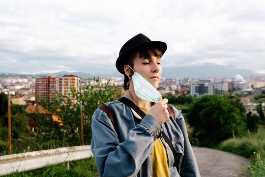 Serious young lady in casual clothes and hat standing with medical mask on street with eyes closed and enjoying fresh air during walk being on quarantine