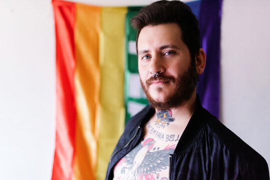 young Caucasian boy with a beard and tattoos poses in front of a rainbow flag of peace with a military jacket.