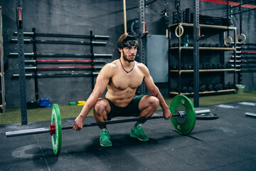 Fit sportsman with strong torso squatting in gym and preparing for weightlifting exercise with heavy barbell looking away