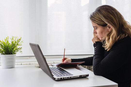 Side view of focused young female in casual outfit sitting at table with laptop and taking notes in planner while working online in light workplace at home